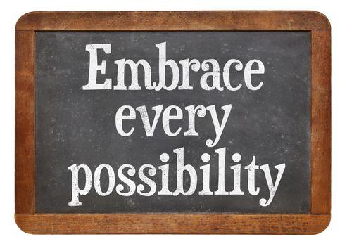 Embrace every possibility - motivational advice on a vintage slate blackboard