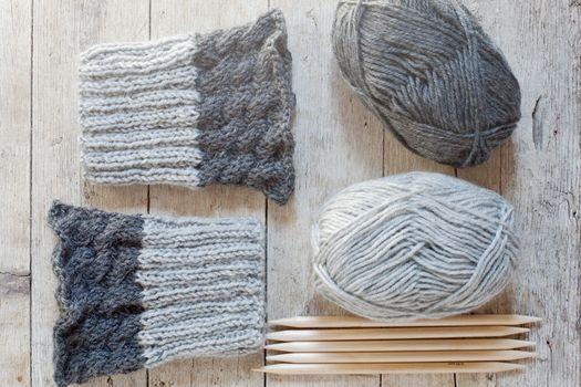 wool grey legwarmers, knitting needles and yarn