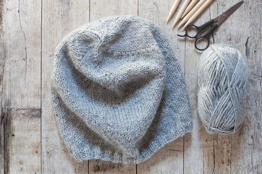 wool grey hat, knitting needles and yarn