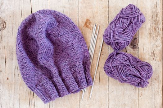 wool purple hat, knitting needles and yarn