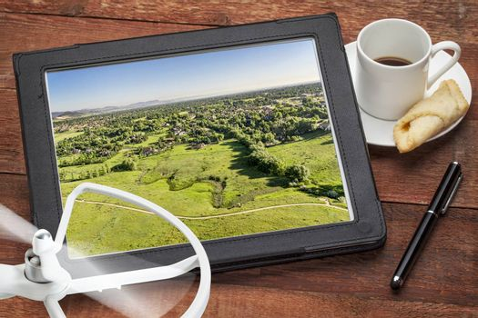 aerial photography concept - reviewing aerial pictures of Fort Collins downtown on a digital tablet with a drone rotor and coffee, screen picture copyright by the photographer