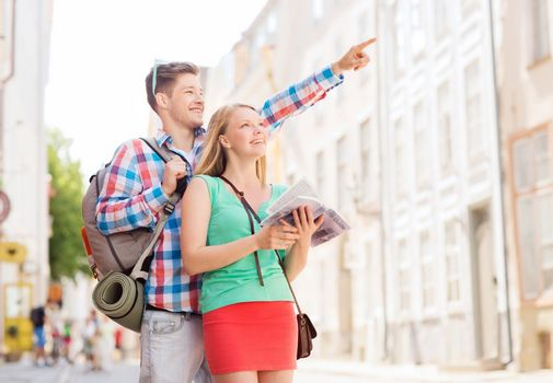 smiling couple with city guide and backpack