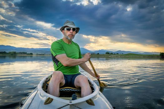 senior male paddling an expedition canoe on lake at dusk with Front Range of Rocky Mountains in background