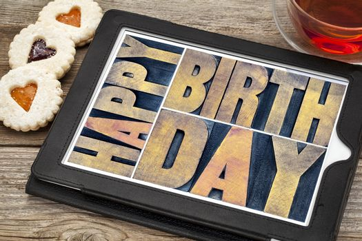 happy birthday typography - isolated text abstract in letterpress wood type printing blocks on a digital tablet with tea and heart cookies