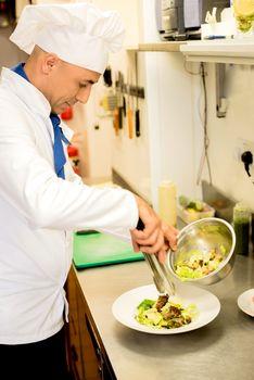Delicatessen salad decorated by male chef