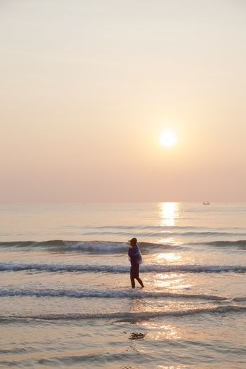 Man walking on the beach. In the morning the sun rises over the ocean.