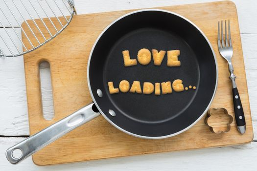 Letter biscuits word LOVE LOADING and cooking equipments.