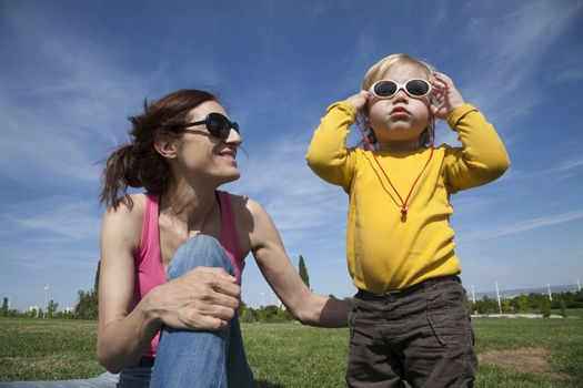two years aged blonde happy baby yellow shirt with white kid sunglasses next to brunette woman mother smiling sitting on green grass lawn in park