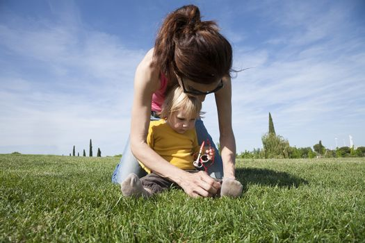 brunette woman mother tying shoelaces to two years aged blonde baby with yellow shirt with white kid sunglasses sitting on green grass lawn in park