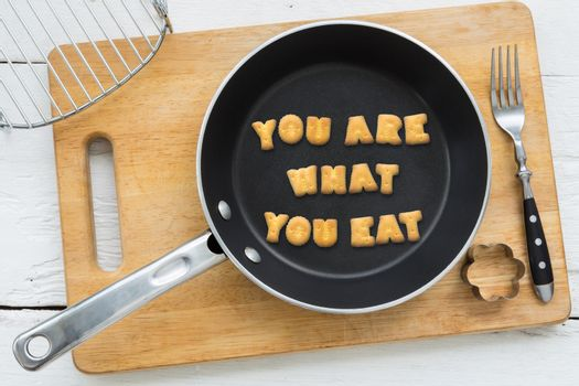 Letter biscuits quote YOU ARE WHAT YOU EAT and cooking equipment