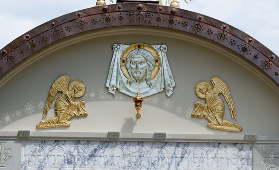 Lunette on Orthodox church with Christ's face and two angels