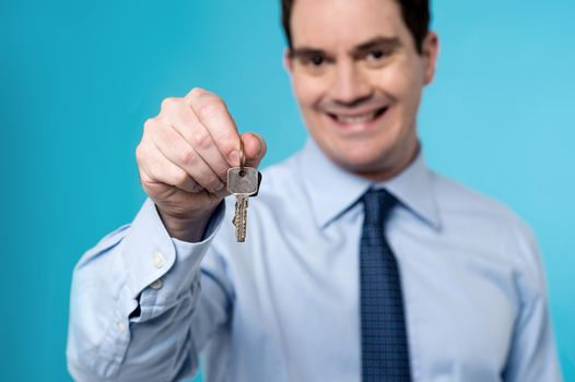 Happy real estate agent offering new house key