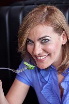 Woman is eating broccoli