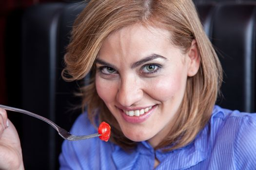 Woman is eating cherry