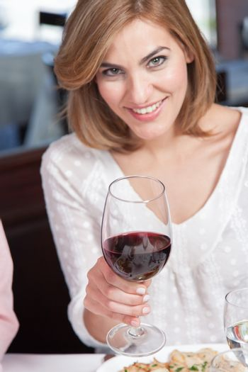 Woman is drinking a cup of wine