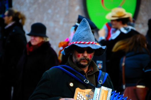 dressed man with an accordion in the carnival