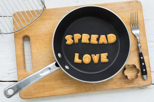Letter biscuits word SPREAD LOVE and cooking equipments.