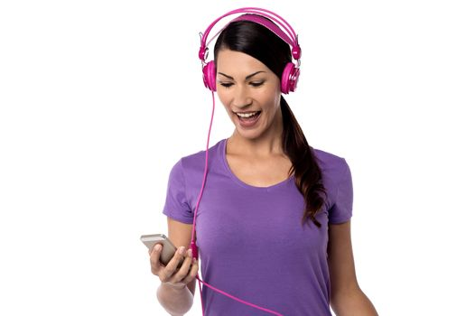Cheerful woman listening music on her cell phone