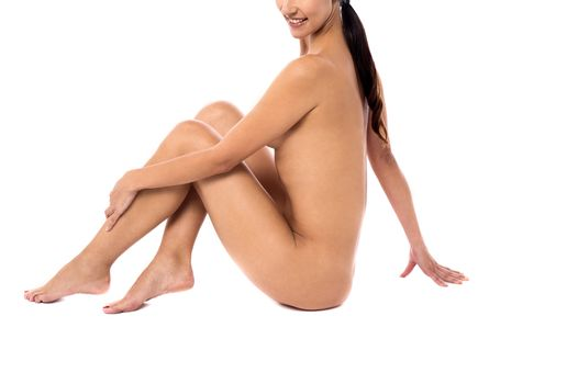 Sideways young naked woman sitting on the floor