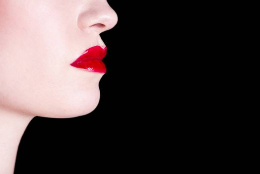 Beautiful female shiny red lips over on black background.