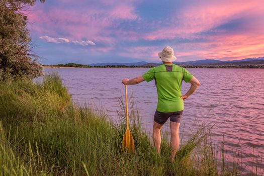 male canoe paddler watching pink sunset sky over a lake and Front Range of Rocky Mountains