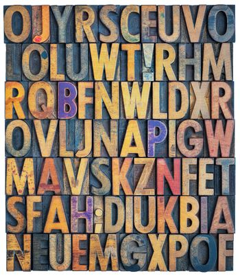 background of antique letterpress wood type printing blocks, random letters of alphabet and punctuation stained by color inks, isolated on white
