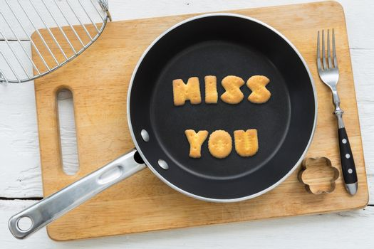 Letter biscuits word MISS YOU and cooking equipments.