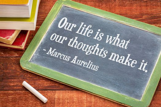 Our life is what our thoughts make it - inspirational word by Marcus Aurelius on a slate blackboard with a white chalk and a stack of books against rustic wooden table
