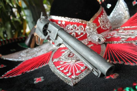 sequin and decorative ornate mexican hat ready for a fiesta with a gun
