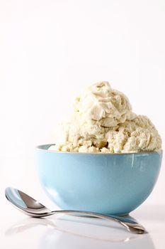 Bowl of vanilla ice cream on table