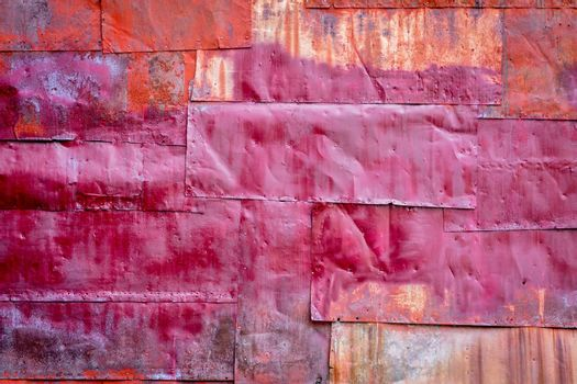 rusty red painted metal background texture - metal sheets covering a wall of an old industrial building