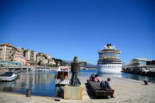 large statue and huge cruise ship in the port of Savona