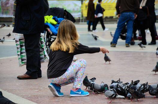 little girl feeding pigeons in the city