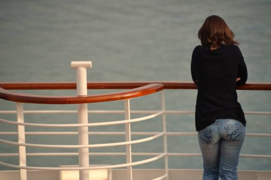 pretty woman from behind at railing of a cruise ship on holiday