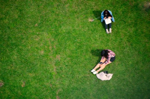 two women sitting on a green meadow view from above