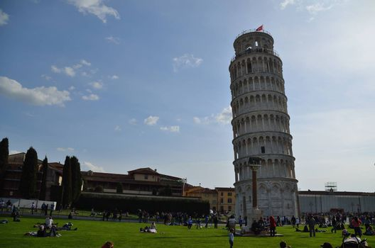 Leaning Tower of Pisa and green meadow with lots of tourists