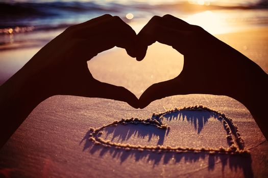 Composite image of hands making heart shape on the beach