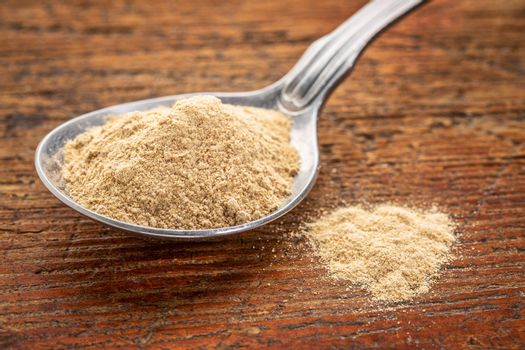 maca root powder on a tablespoon against rustic wood - superfood supplement concept