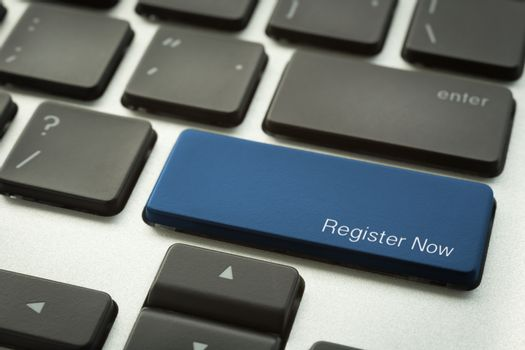 Laptop keyboard with typographic REGISTER NOW button