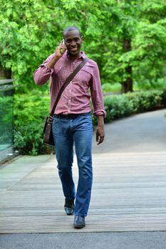 Casual man walking on street while talking on mobile