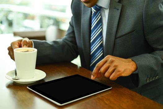 Businessman operating his digital tablet at cafe