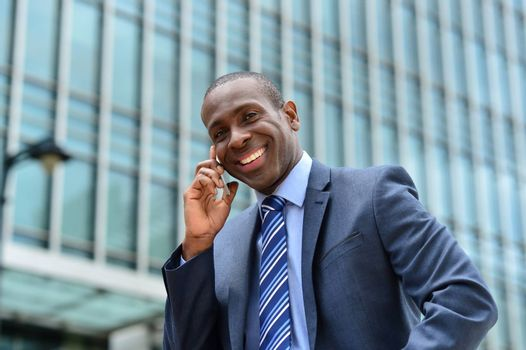 Happy male professional talking on cell phone