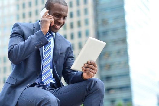 Businessman looking his tablet while talking on mobile