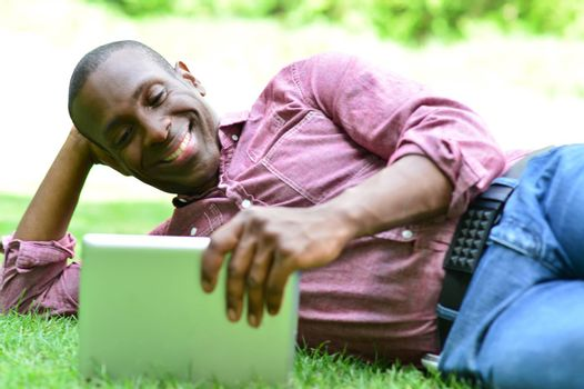 Relaxed man lying on the lawn, watching his tablet