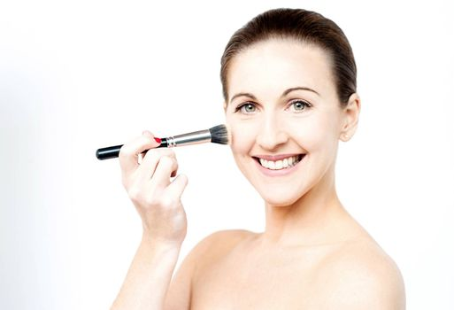 Topless woman applying foundation on face
