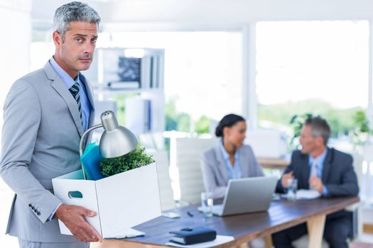 Businessman holding box with his colleagues behind him