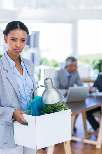 Businesswoman holding box and looking at camera