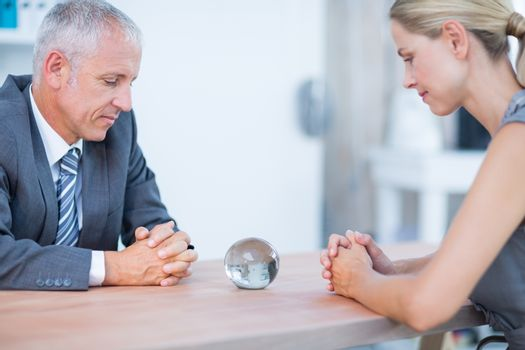 Two business people thinking with a crystal ball