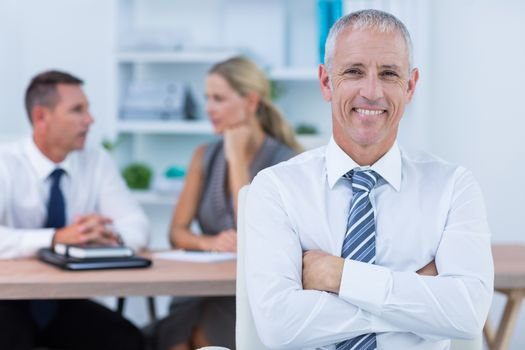 Happy businessman smiling at camera with colleagues behind