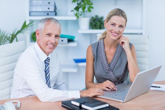 Portrait of colleagues using laptop